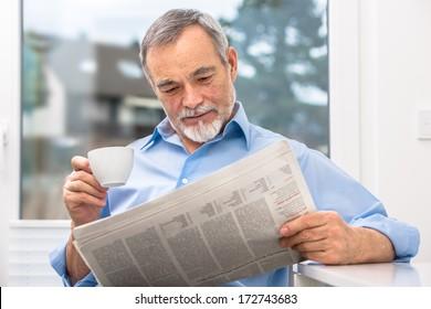Happy senior man at breakfast with newspaper