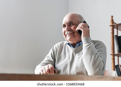 Happy senior man chatting on his mobile phone sitting at a table indoors listening to the conversation with a pleased smile