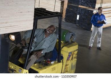 Happy senior man driving forklift