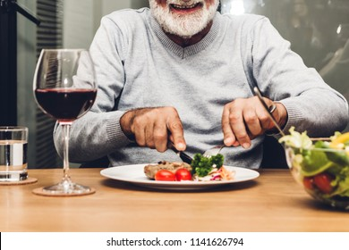 Happy senior man eating pork steak on table at restaurant