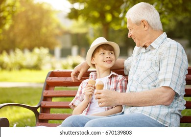 Happy senior man enjoying spending time with his grandson outdoors at the park eating ice cream together copyspace family leisure lifestyle parenting children love weekend summer holidays food concept
