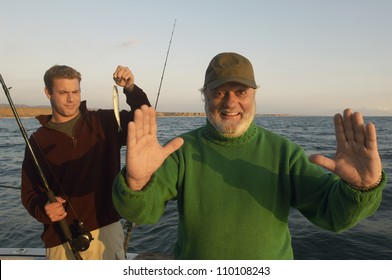 Happy senior man gesturing and person with small catch on yacht
