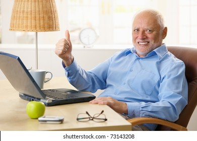 Happy senior man giving thumb up, sitting at desk using laptop computer at home.?