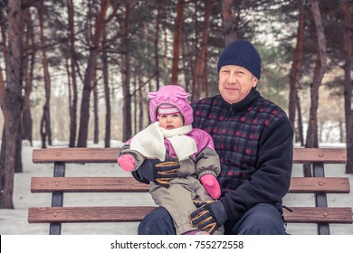 Happy senior man with his granddaughter sitting on bench during walking in winter park in snowy weather  during winter holidays