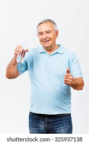 Happy senior man holding bottle of water and showing thumbs up.Thumb up for healthy refreshment