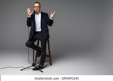 Happy senior man holding a microphone, isolated on white