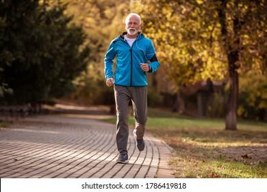 Happy senior man jogging in autumn park. Concept of healthy lifestyle.