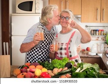 Happy senior man kissing his wife drinking together the juice fruit just made. Wooden table with a large group of colorful fruits and vegetables. Healthy eating