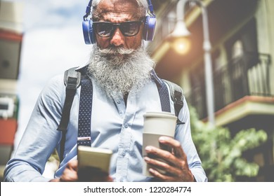 Happy senior man listening music playlist app and drinking coffee at early morning time - Technology, trendy lifestyle,  and joyful elderly lifestyle concept - Focus on headphones