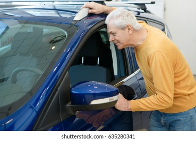 Happy senior man looking inside a new automobile at the dealership showroom. Elderly man buying a new auto cars sales rental retail buyer consumerism pensioner discount offer price comfort travelling