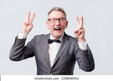 happy senior man making the victory or peace hand sign