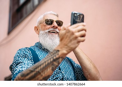 Happy senior man messaging on mobile smartphone outdoor - Bearded hipster fashion male having fun with new technology apps for social media - Concept of tech and elderly fashion people