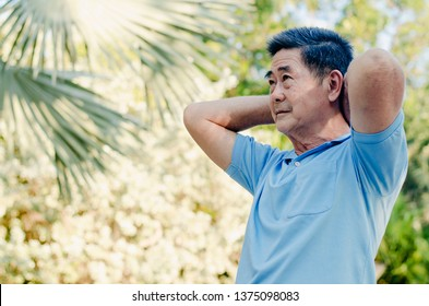 Happy senior man on a walk with armband doing stretching in green nature background.. Autumn nature.