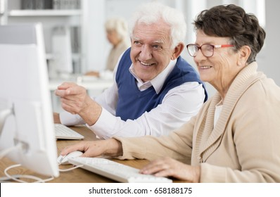 Happy senior man pointing at the computer screen