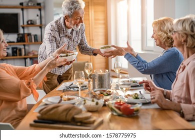 Happy senior man serving lunch to his friends at dining table.