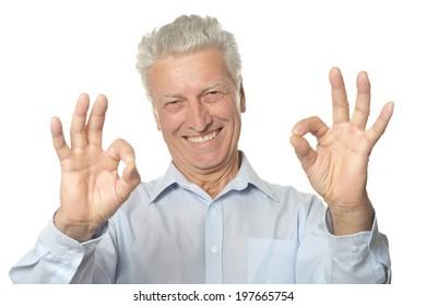 Happy senior man showing ok isolated on white background