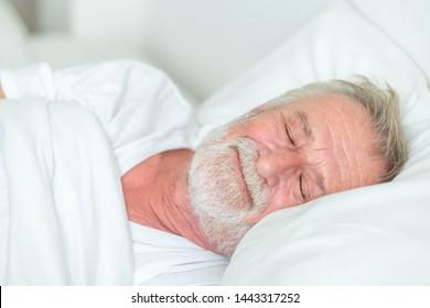 Happy senior man sleeping in bed. Smile.