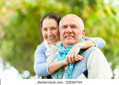 Happy senior man and smiling mature woman together against blured trees background