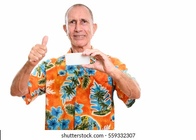 Happy senior man smiling while taking picture with mobile phone and giving thumb up isolated against white background