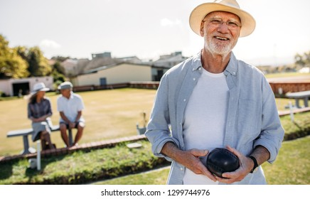 Happy senior man standing in a lawn holding a boules. Elderly man in hat playing boules in a park while his friends are sitting in the background.