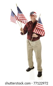 A happy senior man in a stars and stripes hat, displaying three small American flags.  Isolated on white.