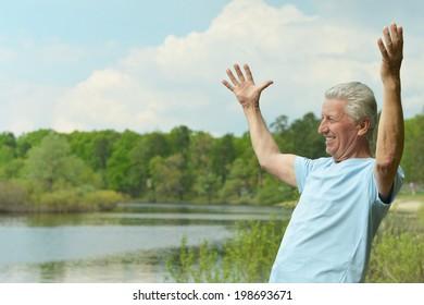 Happy Senior man in summer near lake
