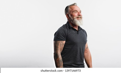 Happy senior man with tattoo on arms standing against white background. Portrait of old muscular male with a white beard looking away.