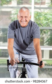 Happy senior man using a home trainer in a gym