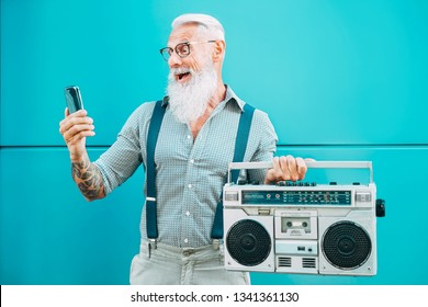 Happy senior man using mobile phone while holding vintage boombox outdoor - Fashion hipster male having fun listening music and using smartphone outside - Technology and elderly lifestyle concept