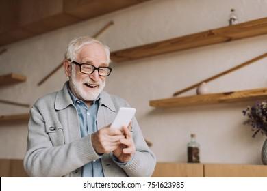 happy senior man using smartphone and looking at camera