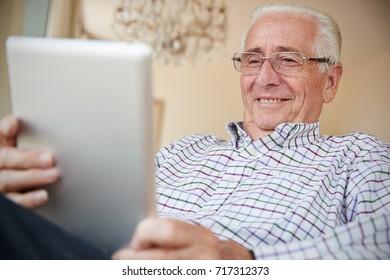 Happy senior man using tablet computer at home, close up