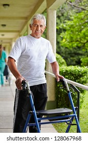 Happy senior man walking with a walker in the park of a clinic