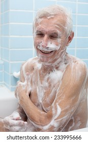 Happy senior man washing his body with soap in bath.