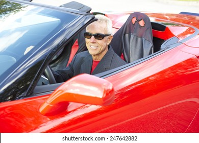 Happy senior man wearing sunglasses while driving red convertible