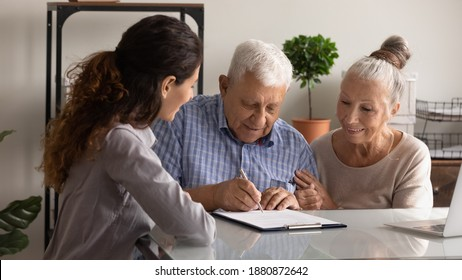 Happy senior man and woman clients sign deal buy house take bank loan mortgage together. Excited elderly couple spouses put signature on document close health insurance agreement in office.