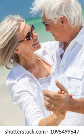 Happy senior man and woman couple dancing and holding hands on a deserted tropical beach with turquoise sea and clear blue sky