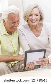 Happy senior man and woman couple sitting together at home on a sofa using a tablet computer