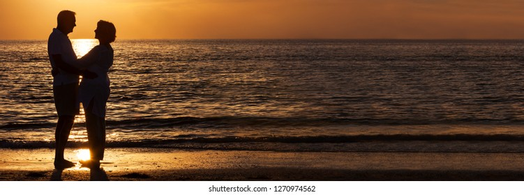 Happy senior man and woman couple together hugging embracing at sunset on a deserted tropical beach panoramic web banner
