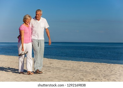 Happy senior man and woman couple walking laughing on vacation on a deserted tropical beach with bright clear blue sky and calm sea