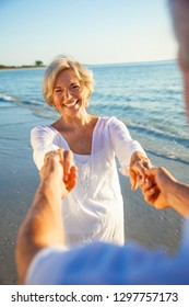 Happy senior man and woman couple dancing and holding hands on a deserted tropical beach at sunset with bright clear blue sky