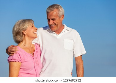 Happy senior man and woman couple walking laughing embracing on vacation with a bright clear blue sky
