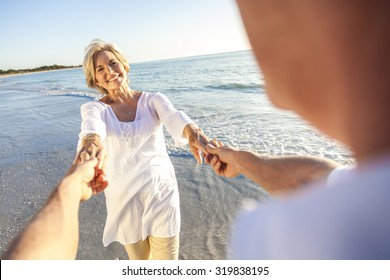 Happy senior man and woman couple walking or dancing and holding hands on a deserted tropical beach with bright clear blue sky