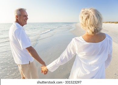 Happy senior man and woman couple walking and holding hands on a deserted tropical beach with blue sky and golden evening light