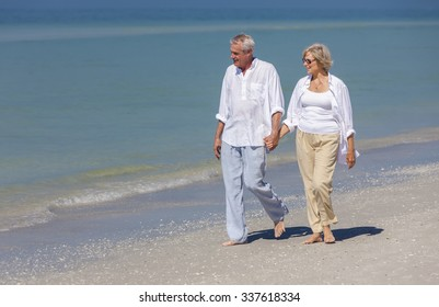 Happy senior man and woman couple walking and holding hands on a deserted tropical beach