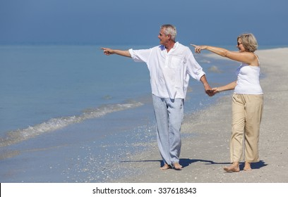 Happy senior man and woman couple walking, holding hands and pointing to sea on a deserted tropical beach with bright clear blue sky