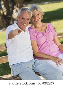 Happy senior man and woman couple sitting together laughing and pointing on a park bench outside in sunshine