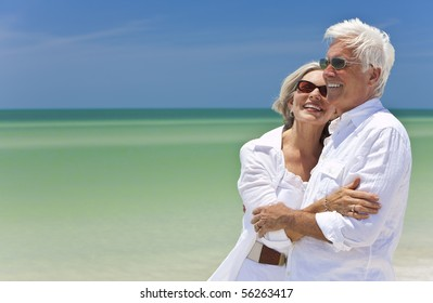 Happy senior man and woman couple together looking out to sea on a deserted tropical beach with bright clear blue sky