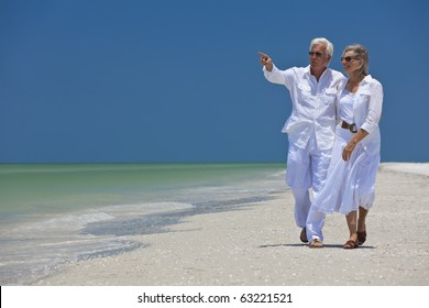 Happy senior man and woman couple walking together looking out to sea on a deserted tropical beach with bright clear blue sky, the man is pointing to the horizon