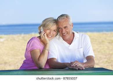 Happy senior man and woman couple sitting together at a table by a beach talking on a cell phone