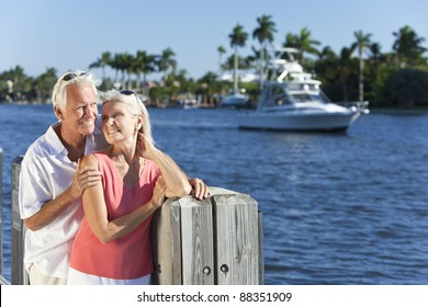 Happy senior man and woman couple together by a river or sea in a tropical location with a boat sailing past
